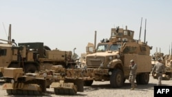 Iraq -- US soldiers stand next to army vehicles during a logistical operation to clear equipment and heavy machinery from the Balad military base, 27Aug2011