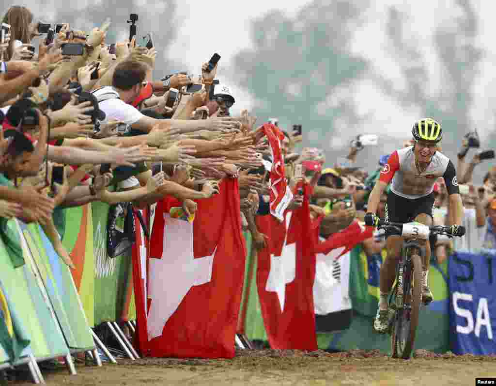 Nino Schurter of Switzerland celebrates his victory in men's cross-country cycling just before crossing the finish line.