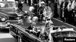 Президент США Джон Кеннеди с супругой Жаклин едут в автомобиле в Далласе. Фото сделано за несколько мгновений до убийства Кеннеди.