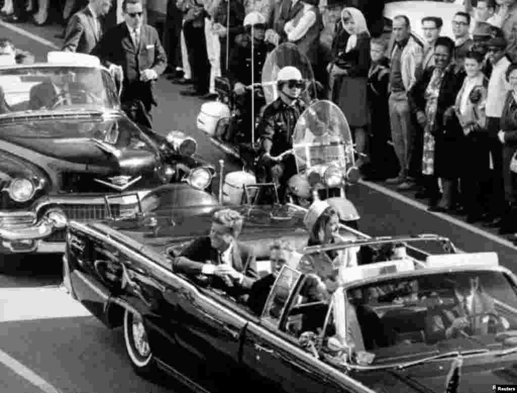 President Kennedy and his wife Jacqueline ride in the motorcade through the city of Dallas just moments before the president was assassinated on November 22, 1963.
