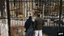 Egypt -- A couple looks at the remains of the ruling National Democratic Party (NDP) headquarters that was burnt during the popular revolt in Cairo, 15Feb2011