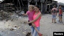 Жінка з дитиною йде повз ринок, зруйнований внаслідок обстрілу 4 червня, Донецьк, Україна