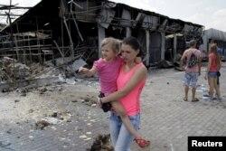 Женщина с ребенком идет вдоль разрушенного бомбежкой дома. Донецк, 4 июня 2015 года.