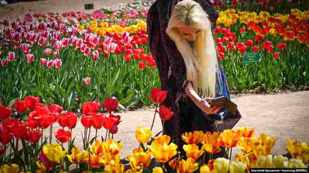 Musafirler sergide, acayip çiçekler ile resimge çıqmaq içün gacetlerini ellerinden aman-aman taşlamadılar