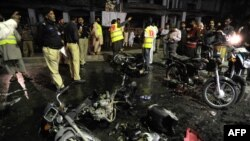 Pakistani Police officials inspect the site of a bomb explosion in Rawalpindi late on May 15, 2014.