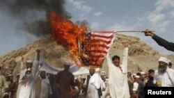 Әфганстанда бер төркем протест белдерүче американ әләмен яндыра
