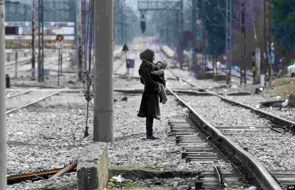 A migrant woman carries her child as they wait to cross the Greek-Macedonian border near Gevgelija on February 8. (AFP/Robert Atanasovski)