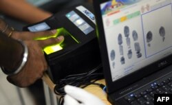 A foreign worker provides his thump print impression as he registers under a new biometric program in Malaysia.