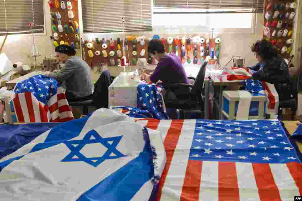 Employees sew Israeli and U.S. flags in preparation for the upcoming visit of U.S. President Barack Obama in the town of Kfar Saba, Israel. Obama's three-day visit to Israel and the Palestinian territories will begin on March 20, Israel said. (AFP/Jack Guez)