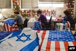 Рабочие израильской текстильной фабрики подшивают флаги Израиля и США накануне визита Обамы