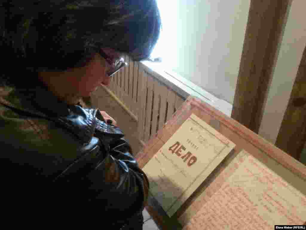 Женщина рассматривает стенд с личным делом заключенного Карлага.