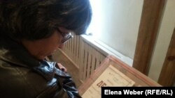 Женщина читает стенд с личным делом заключенного Карлага, одного из лагерей системы ГУЛАГ. Иллюстративное фото.