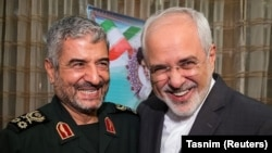 Islamic Revolutionary Guard Corps (IRGC) commander Mohammad Ali Jafari (L) and Iranian Foreign Minister Mohammad Javad Zarif smile during a coordination meeting for the 40th anniversary of the Islamic Revolution, in Tehran, October 9, 2017