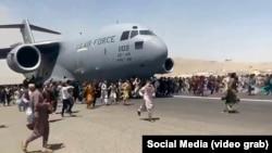 Кабулдагы аэропортто АКШнын аскердик учагынын жолун тосууга аракет кылган ооган жарандар. 16-август, 2021-жыл.
