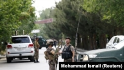 FILE: Afghan policemen stand guard near the site of an attack in Kabul on June 12.
