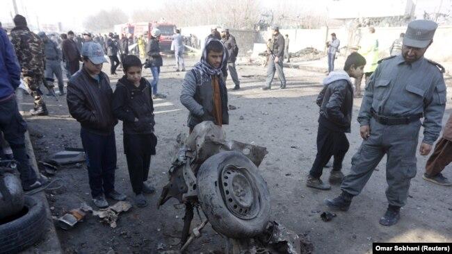 Policija i lokalno stanovništvo gleda u ostatke automobila na mjestu gdje se dogodio samoubilački napad u kojem je jedna osoba poginula a 13 ranjeno, 28. 12. 2015.