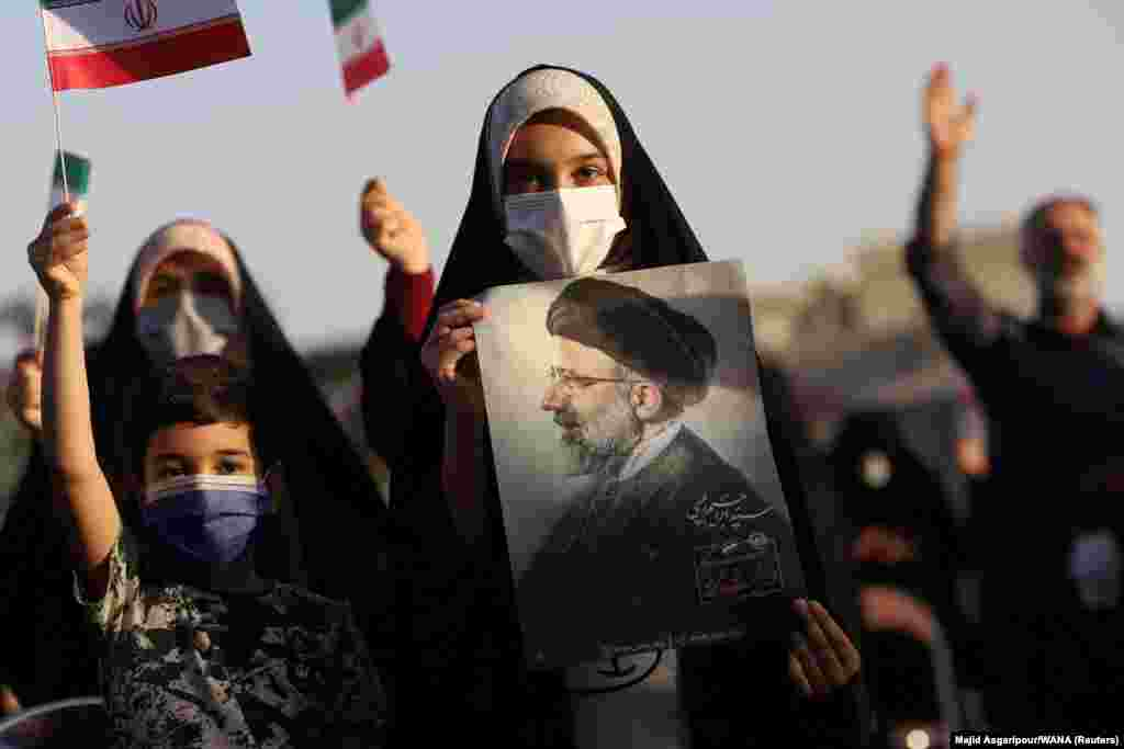 A supporter of Ebrahim Raisi displays his portrait during a rally in Tehran to celebrate his Iranian presidential election victory.