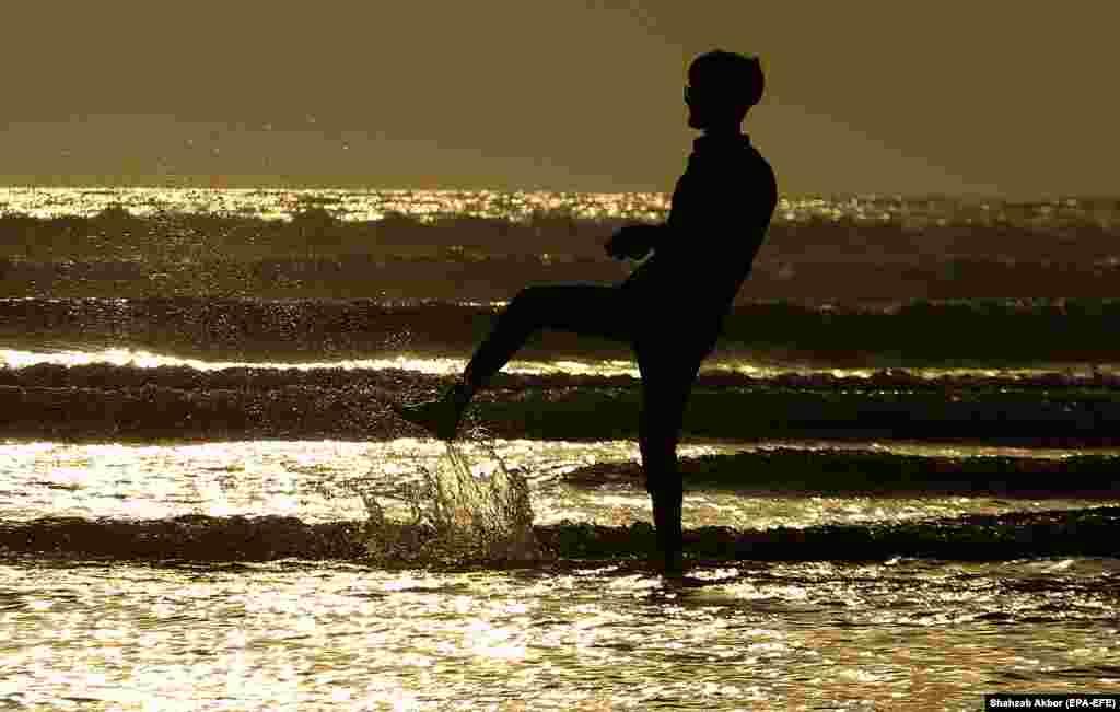 A man paddles as the sun sets at the beach in Karachi, Pakistan. (epa-EFE/Shahzaib Akber)