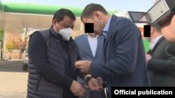Raimbek Matraimov (left) is shown as he was detained in Bishkek on October 20.