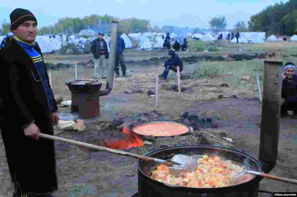 Узбекский мигрант готовит еду на костре в лагере.