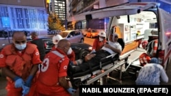 LEBANON -- Medics shift an injured person from Najjar Hospital to another hospital in Al-Hamra area in Beirut after Port explosion, in Beirut, August 4, 2020.