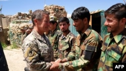 Scott Miller, commander of U.S. and NATO forces in Afghanistan (left), shakes hands with Afghan National Army soldiers while visiting a checkpoint in the Nerkh district of Wardak Province. (file photo)
