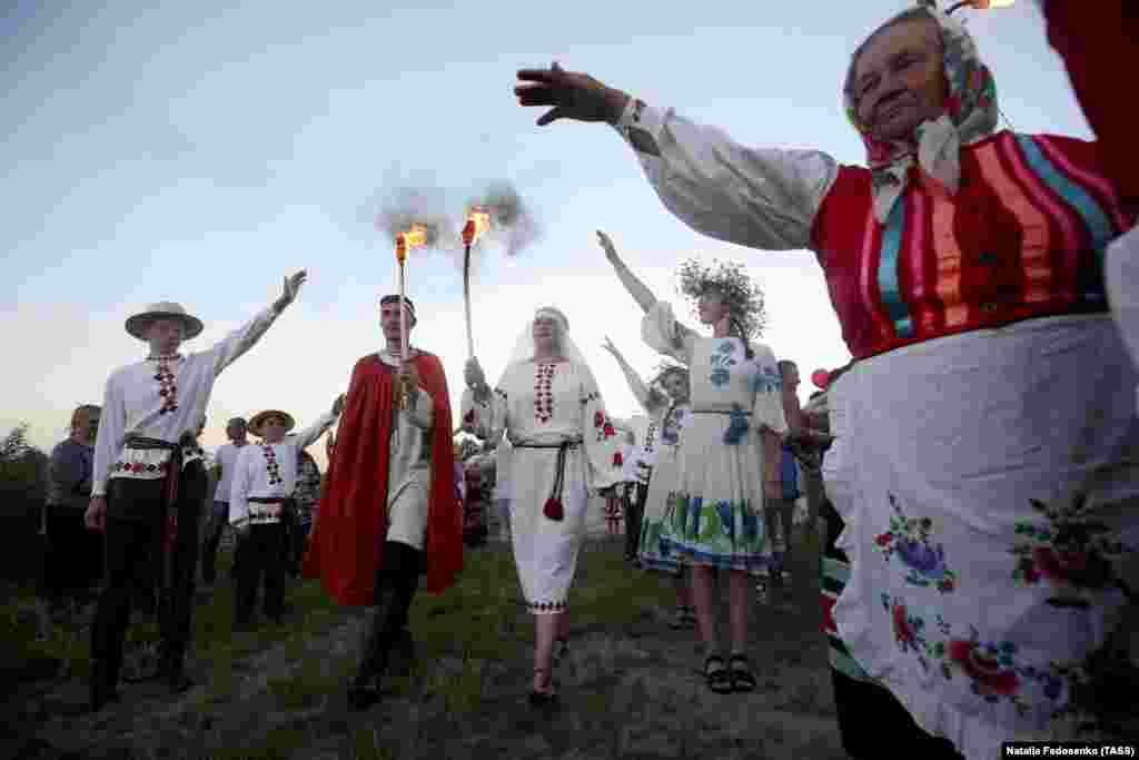 People in ethnic costumes dance by the Pripyat River.