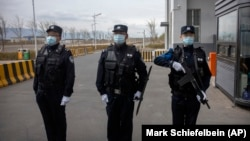 Police officers stand at the outer entrance of detention center in China's western Xinjiang region.