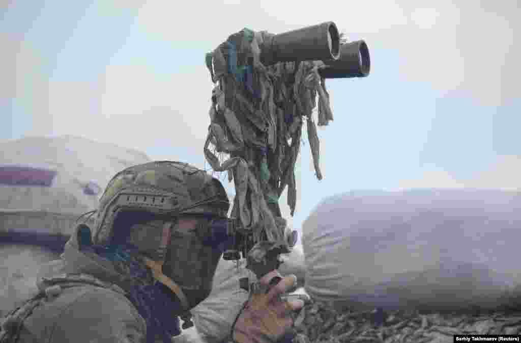 Украинский военный наблюдает за позициями на линии разграничения под Донецком. Город находится под контролем поддерживаемых Россией сепаратистов. 6 апреля 2021 года.