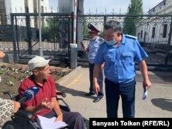 Представитель прокуратуры стоит рядом с Дастаном Орынбасаровым. Нур-Султан, 8 июля 2021 года