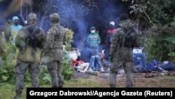 Польские пограничники охраняют группу мигрантов, пытавшихся перейти границу между Беларусью и Польшей