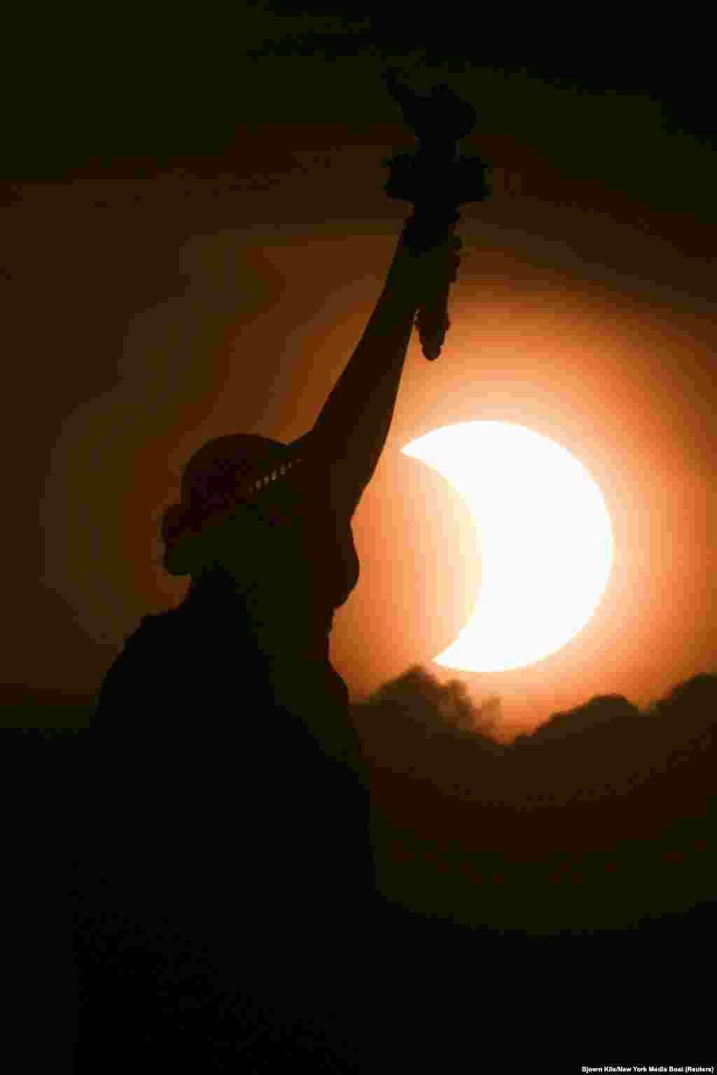 Частково затемнене сонце сходить за статуєю Свободи в Нью-Йорку, США