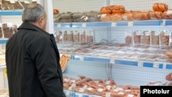 Armenia -- A man looks at meat products at a food store in Yerevan.