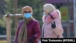 Женщины в защитных масках на улице в Алматы. 18 марта 2021 года.