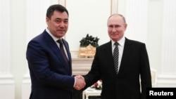 Kyrgyzstan's Sadyr Japarov (left) skaes hands with Russia's Vladimir Putin in Moscow on February 24.