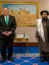 U.S. Secretary of State Mike Pompeo and Mullah Abdul Ghani Baradar, a co-founder of the Taliban and a former deputy to Mullah Omar. Baradar, who spent years in a Pakistani prison, is the Taliban's political chief and was the head negotiator in talks with the United States.