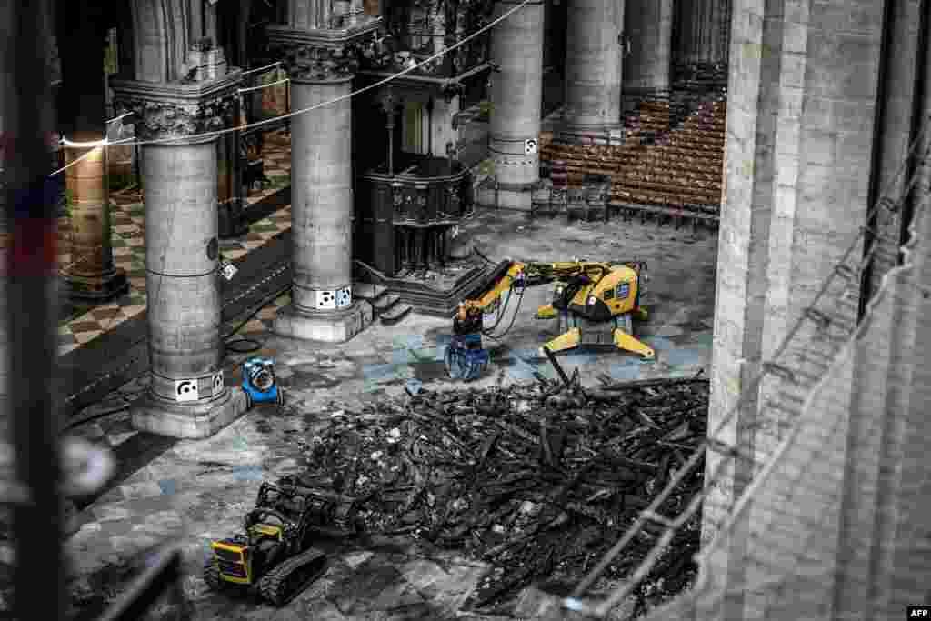 Отломките от разрушенията бяха разчиствани в продължение на месеци след като огънят унищожи голяма част от интериора на 850-годишната готическа катедрала. Този кадър е от 17 юли 2019 г. и показва работници, които извършват подготвителни дейности преди да започне същинската работа по възстановяването на Нотр Дам.