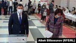 Президент Садыр Жапаров с супругой Айгуль на избирательном участке.