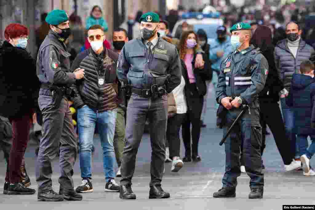 Rómában a Via del Corson rendőrök ellenőrzik a maszk viselését.