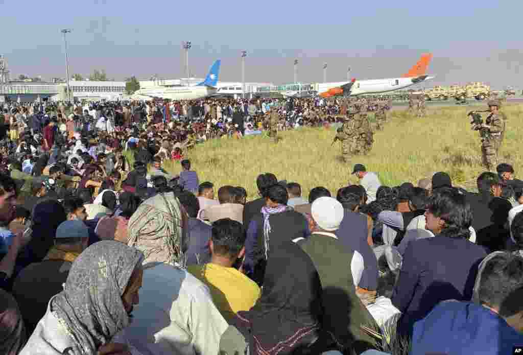Американски войници охраняват периметъра на международното летище в Кабул, Афганистан. В понеделник американските военни и официални лица бяха съсредоточени върху летището в Кабул, където хиляди афганистанци се втурнаха по асфалта и се вкопчиха в американските военни самолети, подготвени за излитане на служители на посолството на САЩ, което затвори в неделя.