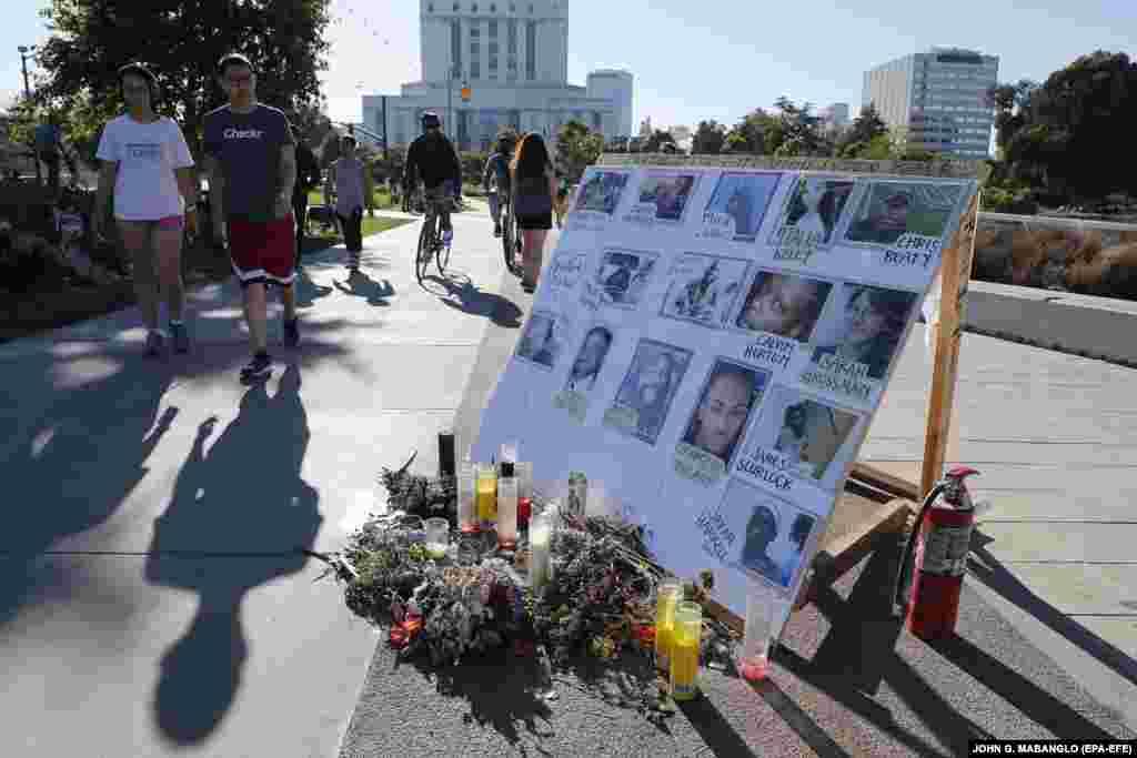 Люди проходять повз меморіал зроблений в пам'ять про людей, які померли через поліцейське свавілля, неподалік місця протесту в Окленді. Протести виникли після смерті Джорджа Флойда, який загинув під час затримання в Міннеаполісі 25 травня 2020 року. Окленд, штат Каліфорнія. 10 червня 2020 року