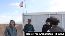 Naqibullah (right) explains demining techniques to three Afghan police officers at a checkpoint outside Tarin Kowt.