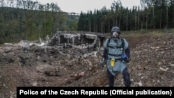 A pyrotechnician inspects the site after the blast at an ammunition depot near Vrbetice, Czech Republic, on October 20, 2014.