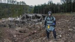 Un pirotehnist inspectează locul după explozia de la un depozit de muniție de lângă Vrbetice, Republica Cehă, ce a avut loc pe 20 octombrie 2014.