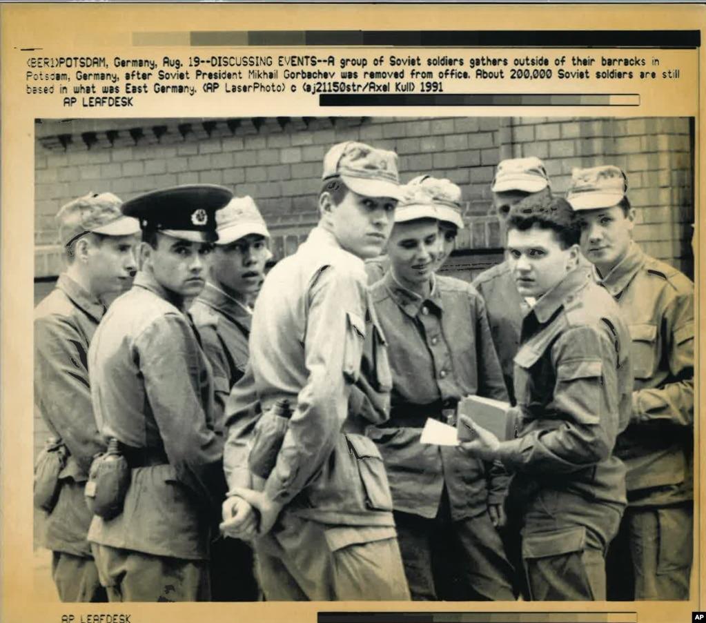 Радянські солдати обговорюють новини про путч 19 серпня в Потсдамі в Німеччині, у східній частині країни, яка ще за кілька місяців до того була відома як НДР. На серпень 1991 року в цій частині Німеччини все ще перебувало близько 200 тисяч радянських військових