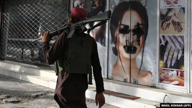 """Бұрын сән салоны болған ғимараттың тұсынан қару ұстап өтіп бара жатқан """"Талибан"""" адамы. Кабул, Ауғанстан, 18 тамыз 2021 жыл."""