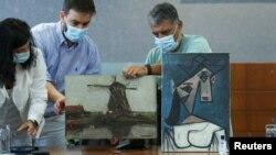 """Специалисти показват в Атина """"Мелница"""" на Пийт Мондриан (вляво) и """"Глава на жена"""" на Пабло Пикасо. Двете картини бяха показани за пръв път на 29 юни 2021, след като през 2012 г. бяха откраднати от Националната галерия на Гърция."""