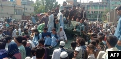 Taliban fighters and locals sit on an Afghan National Army vehicle on a street in Jalalabad Province on August 15..