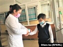 Медсестра измеряет температуру тела ученика в школе № 58. Шымкент, 2 марта 2021 года.