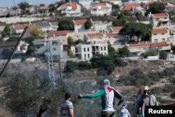 Palestinski demonstranti stoje ispred jevrejskog naselja za vrijeme protesta, u mjestu Kafr Qaddum na Zapadnoj obali okupiranoj Izraelom 13. novembra 2020.
